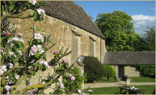 Apple blossom frames the courtyard at Cotswold Woollen Weavers in Filkins